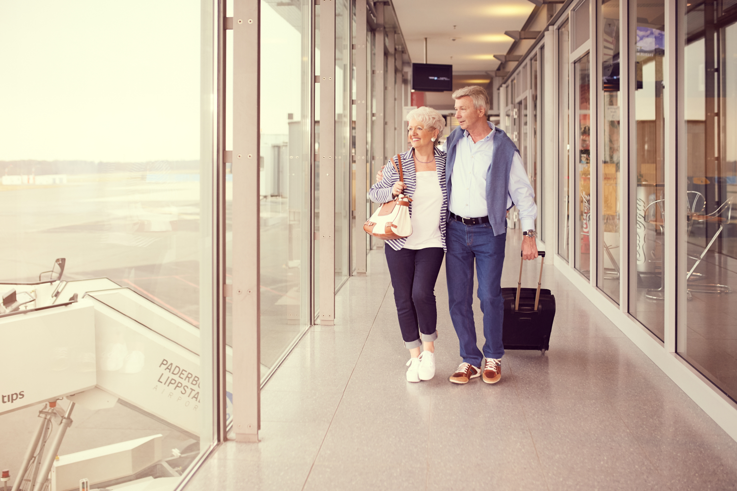 couple with trolley walking in terminal