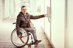 wheelchair user pushes help button at parking place