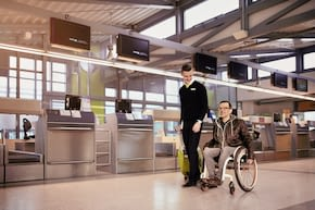 wheelchair user is accompanied by staff